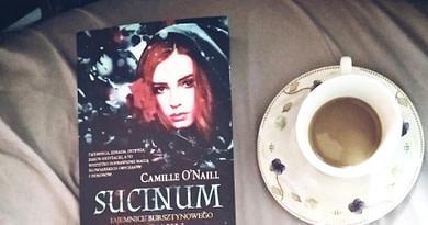 Sucinum - Recenzja książki -Książka na tle pościeli, obok niej kubek z kawą
